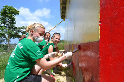 Projects Abroad Jamaica volunteers help paint the recently constructed bathrooms at Bryce Primary School