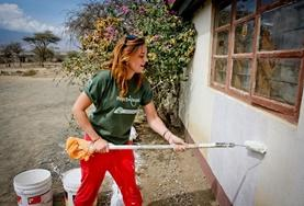 A building volunteer gives a new classroom a fresh coat of paint in Tanzania.