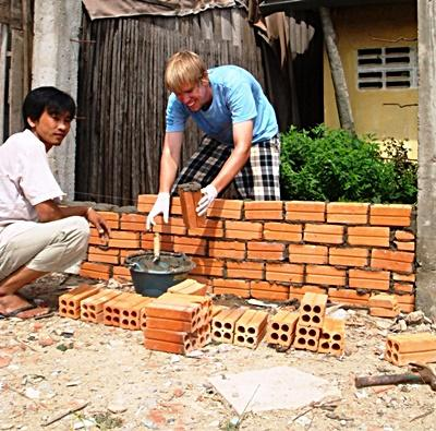 Volunteer and staff member help construct a building on a Community Building Project abroad