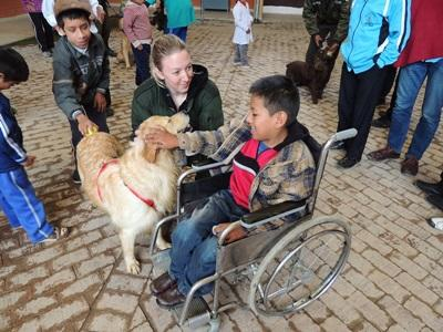 A Projects Abroad Canine Therapy volunteer helps a child with special needs interact with a trained therapy dog in Bolivia.