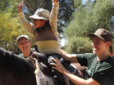 Two Projects Abroad Volunteers help a child with special needs during a therapy session at their Equine Therapy Project in Bolivia.