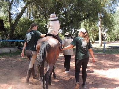 Projects Abroad volunteers help a child ride a trained therapy horse during a treatment session at the Equine Therapy Project in Bolivia.