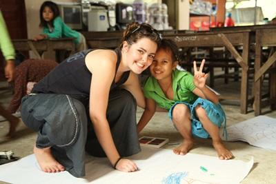 A Projects Abroad volunteer helps a child with an arts and crafts activity at a care centre in Cambodia, Asia.
