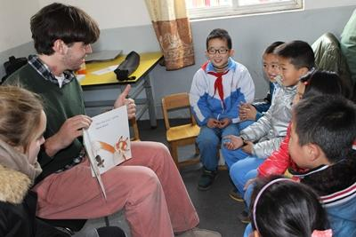 A group of local children enjoy listening to a Projects Abroad volunteer read a story at a kindergarten in China.