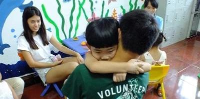 A Chinese child is held by a Projects Abroad volunteer