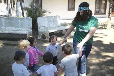 Costa Rican children enjoy playing an outdoor game with a Projects Abroad volunteer.