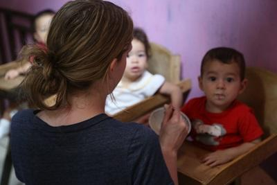 A young Costa Rican child is fed a meal by a Projects Abroad volunteer