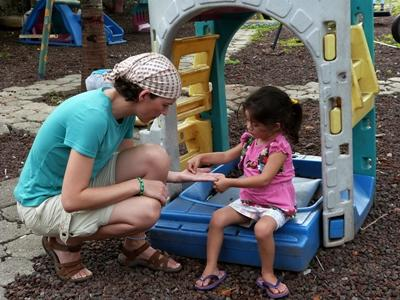 Projects Abroad volunteer on the playground with a young girl at a kindergarten in Ecuador.