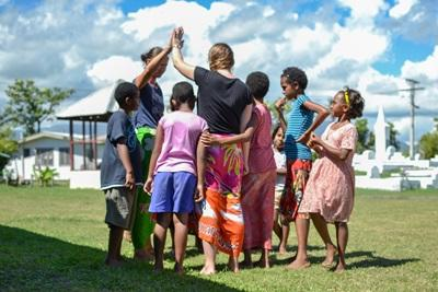 Two Projects Abroad volunteers play a game ourdoors with local children at a day care centre in Fiji.