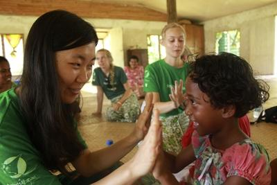 A Fijian girl enjoys playing a clapping game with a volunteer.