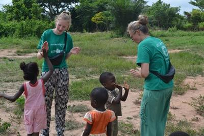 A mother and daughter volunteering together with Projects Abroad play outdoors with local children at their placement in Ghana.