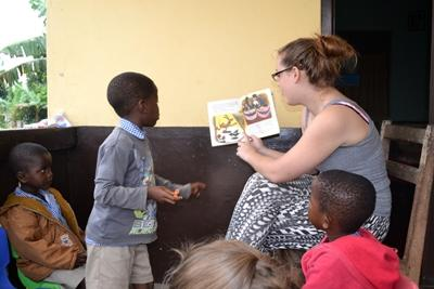 Projects Abroad volunteer reads a story aloud to children in Ghana.