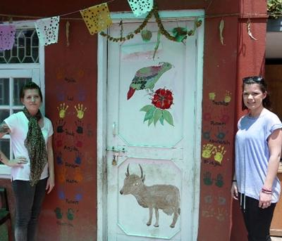 Projects Abroad volunteers paint the door of a facility that cares for and supports children affected by HIV and AIDS in Nepal.