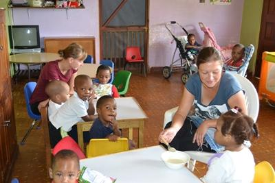 Projects Abroad volunteer supervises young children and makes sure they eat their meal at a care facility in Jamaica.