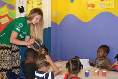 Projects Abroad volunteer helps a child with a painting activity at a day care centre in Jamaica.