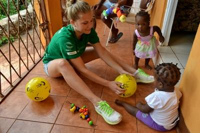 Projects Abroad volunteer plays a ball game with young children at a care facility in Jamaica.