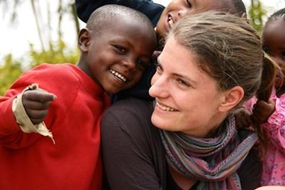 Female volunteer smiling with a Kenyan boy  at a kindergarten in Kenya