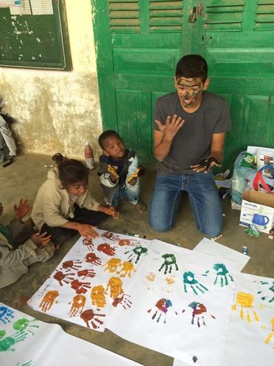 Projects Abroad volunteer does a painting activity with children at a school in Madagascar.