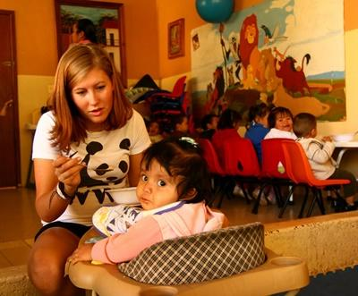 Projects Abroad volunteer feeds a baby girl at a care centre in Mexico, North America.