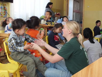 A little boy enjoys playing a game with a Care volunteer in Mongolia, Asia