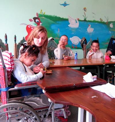 A Projects Abroad volunteer helps feed a child with special needs in Morocco.