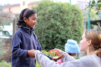 A Nepalese girl enjoys playing a clapping game with a volunteer.