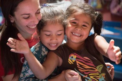 Children at a care placement in Costa Rica laughing with a Care volunteer