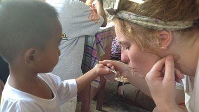 A Projects Abroad volunteer blows gently on food to cool it before feeding a child at a care centre in the Philippines, Asia.