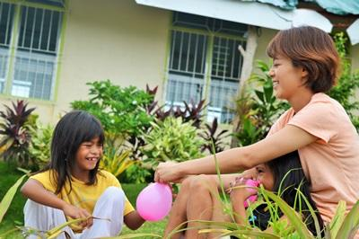 Projects Abroad volunteer and child play with water balloons at a care centre in the Philippines, Southeast Asia.
