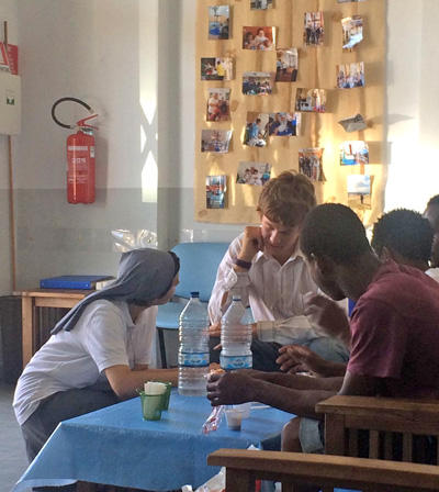 A Projects Abroad volunteer has a discussion with refugees and migrants in Italy, Europe