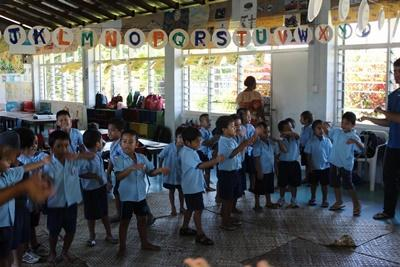 A group of young children participate in an activity led by a Projects Abroad volunteer at their school in Samoa.