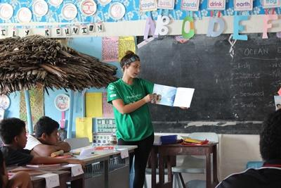 A Projects Abroad volunteer reads aloud to children in a classroom in Samoa.