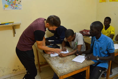 Projects Abroad volunteer helps a group of disadvantaged children with a homework exercise in Senegal, Africa.