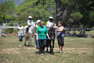 Projects Abroad volunteers help a group of children with special needs during a therapy session at the Equine Therapy Project in South Africa