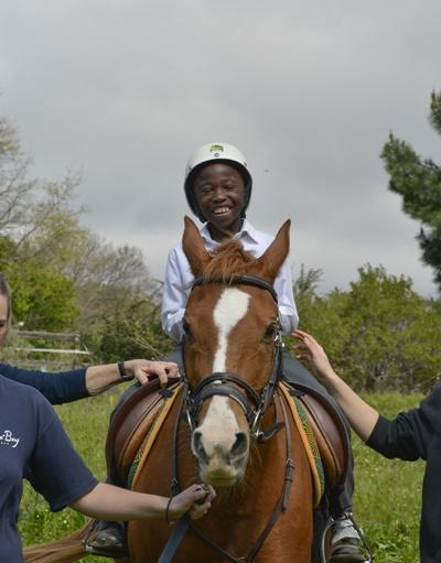 A local child participates in a therapy session with Projects Abroad volunteers at an equine therapy centre in South Africa.