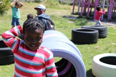 A South African child enjoys playing outside with Projects Abroad volunteers at a local day care centre.