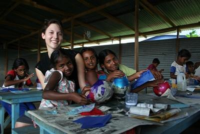 A group of young girls in Sri Lanka get help for an activity from a Projects Abroad volunteer at their school.