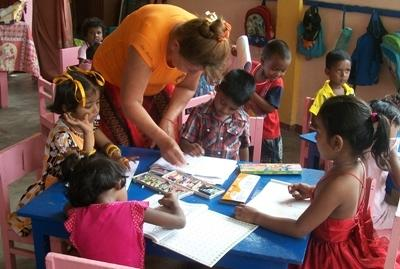 Sri Lankan children complete an activity with the help of a Projects Abroad volunteer.