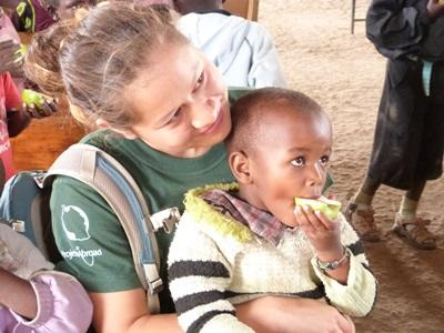A Projects Abroad volunteer holds a boy while he eats fruit at a kindergarten in Tanzania.