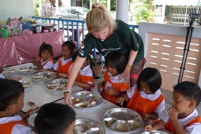 Projects Abroad volunteers help and supervise children during lunch at a kindergarten in Thailand.