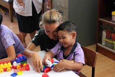 A local child enjoys playing with building blocks with a Projects Abroad volunteer at a kindergarten in Thailand, Asia.
