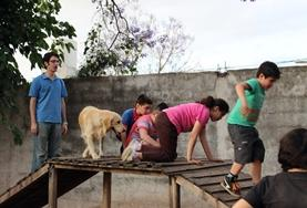 Children interact with a trained dog at the Canine Therapy volunteer project in Argentina.