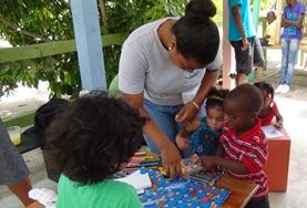 A volunteer helps children with an activity in Belize during her Care Project.