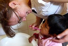 A volunteer on the Care Project in Bolivia teaches a young child about the importance of hygiene and brushing teeth.