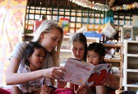 Children listen to volunteers reading a story in Cambodia.