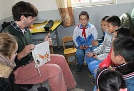A volunteer reads aloud to children in China during his Care Project.