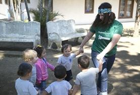 A volunteer plays a game with children outdoors in Costa Rica.