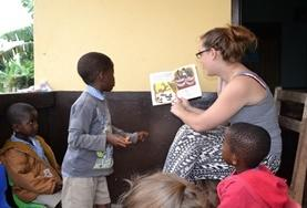 A volunteer on a Care Project reads a story to children in Ghana.