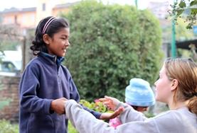 A volunteer plays outdoors with children in Nepal.