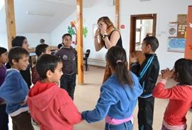 A volunteer leads a group activity with children at a day care centre in Romania.